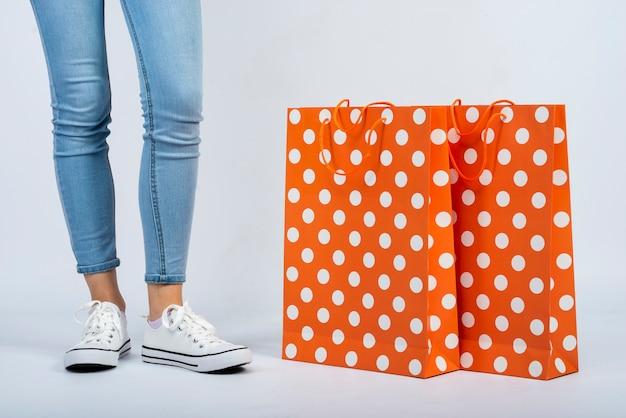 Close-up boodschappentassen model in de buurt van de benen van de vrouw
