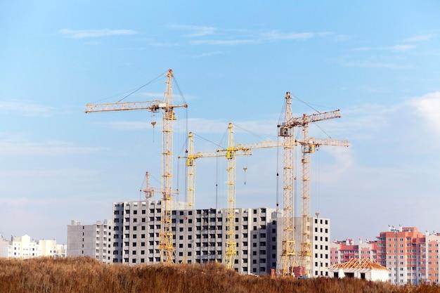 Close-up bouwkranen tijdens de bouw van een nieuw woongebouw met meerdere verdiepingen
