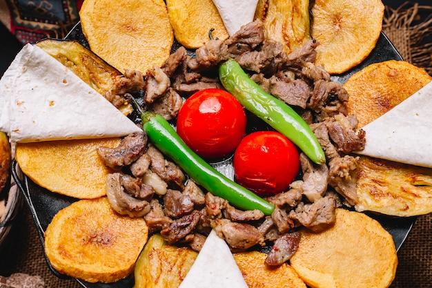 Close-up bovenaanzicht een traditionele azerbaijani schotel vlees salie met pitabroodjes aardappelen tomaten en groene paprika