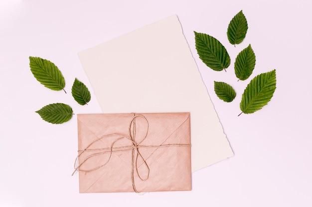 Close-up bovenaanzicht gebonden envelop en bladeren