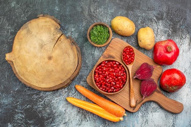 Close-up bovenaanzicht groenten granaatappel zaden wortelen bieten aardappelen kruiden de snijplank