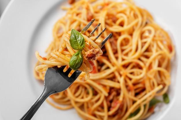 Close-up bovenaanzicht italiaanse keuken spaghetti bolognese op vork met basilicum