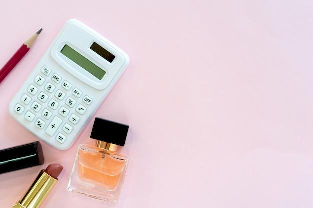 Close-up bovenaanzicht op rekenmachine met potlood, lippenstift en parfum op roze achtergrond