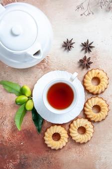 Close-up bovenaanzicht snoep koekjes een kopje thee theepot steranijs