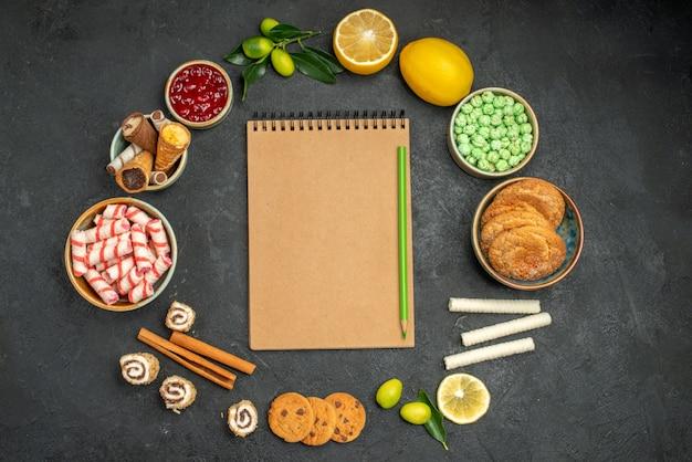 Close-up bovenaanzicht snoepjes jam citroenen koekjes snoepjes wafels rond notebook