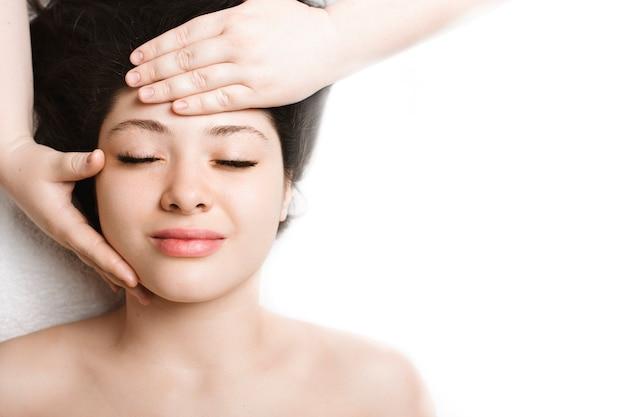 Close-up bovenaanzicht van een mooie vrouw met anti-leeftijd gezichtsmassage in een wellness-kuuroord tijdens het reizen in haar vakantietijd.