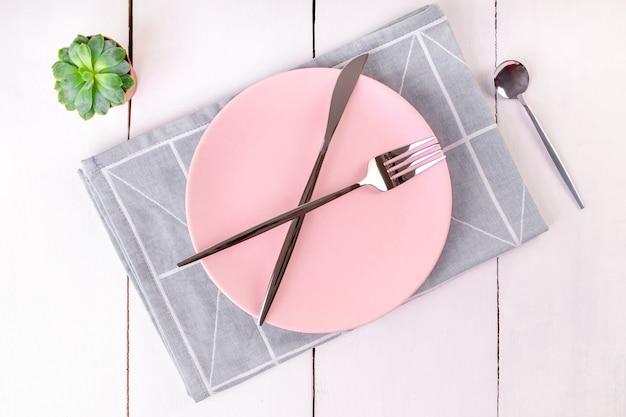 Close-up bovenaanzicht van het serveren van lege roze plaat met gekruiste mes en vorken op gevouwen linnen servet met geometrisch patroon. selectieve aandacht. mockup, kopieerruimte, minimalisme.