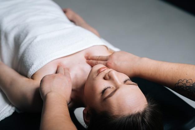 Close-up bovenaanzicht van jonge vrouw die op de massagetafel ligt tijdens schouder- en nekmassage