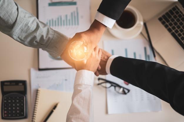 Close-up bovenaanzicht van mensen uit het bedrijfsleven hun handen in elkaar zetten, teamwerk ideeën,