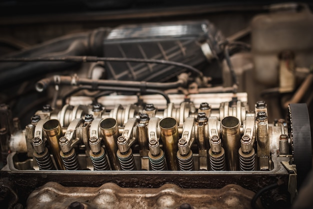 Close-up bovenaanzicht van motoronderdelen kopstukken zuigers blok en kettingoverbrenging.