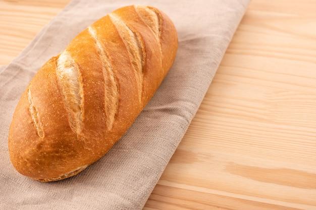 Close-up brood op textiel servet houten tafel achtergrond. zelfgemaakt brood. brood recept concept. kopieer ruimte.