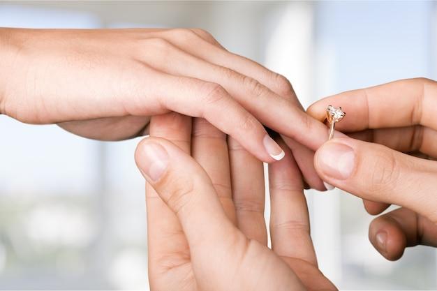 Close-up bruidegom die de trouwring om de vinger van de bruid doet