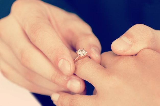 Close-up bruidegom die de trouwring omdoet aan de bruid