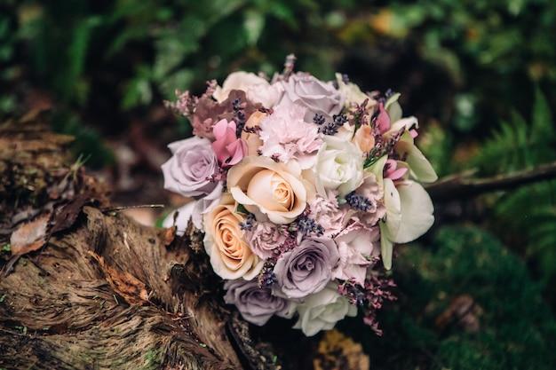 Close-up bruids boeket van rozen in lila roze op een vage achtergrond van bos en mos, selectieve nadruk