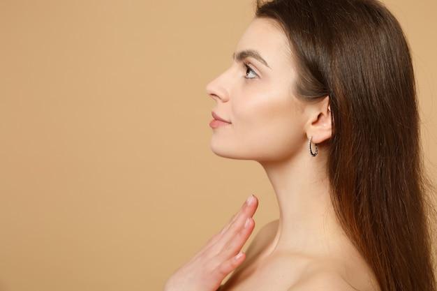 Close-up brunette half naakte vrouw 20s met perfecte huid, hand op nek geïsoleerd op beige pastel muur, portret. huidverzorging gezondheidszorg cosmetische procedures concept. .