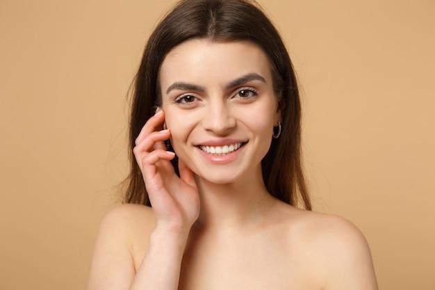 Close-up brunette half naakte vrouw 20s met perfecte huid, hand op wang geïsoleerd op beige pastel muur, portret. huidverzorging gezondheidszorg cosmetische procedures concept. .