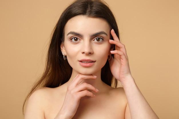 Close-up brunette half naakte vrouw 20s met perfecte huid, handen op gezicht geïsoleerd op beige pastel muur, portret. huidverzorging gezondheidszorg cosmetische procedures concept. .