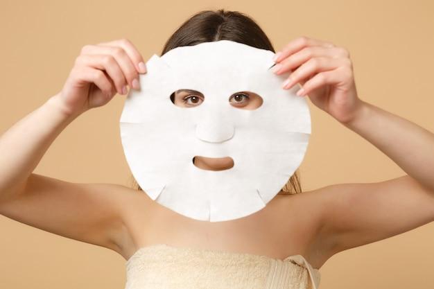 Close-up brunette half naakte vrouw 20s met perfecte huid, naakt make-up geïsoleerd op beige pastel muur, portret. huidverzorging gezondheidszorg cosmetische procedures concept.