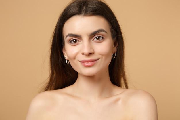 Close-up brunette half naakte vrouw 20s met perfecte huid, naakt make-up geïsoleerd op beige pastel muur, portret. huidverzorging gezondheidszorg cosmetische procedures concept. .