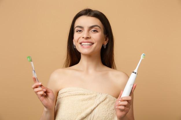 Close-up brunette half naakte vrouw met perfecte huid naakt make-up borstels geïsoleerd op beige pastel muur
