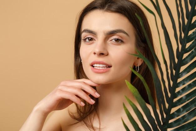 Close-up brunette half naakte vrouw met perfecte huid, naakt make-up en palmblad geïsoleerd op beige pastel muur