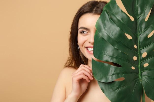 Close-up brunette half naakte vrouw met perfecte huid, naakt make-up en palmblad geïsoleerd op beige pastel muur Gratis Foto