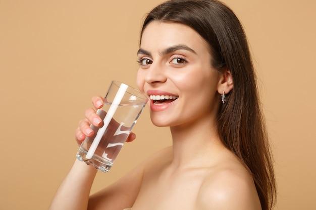 Close-up brunette half naakte vrouw met perfecte huid naakt make-up glas water geïsoleerd op beige pastel muur