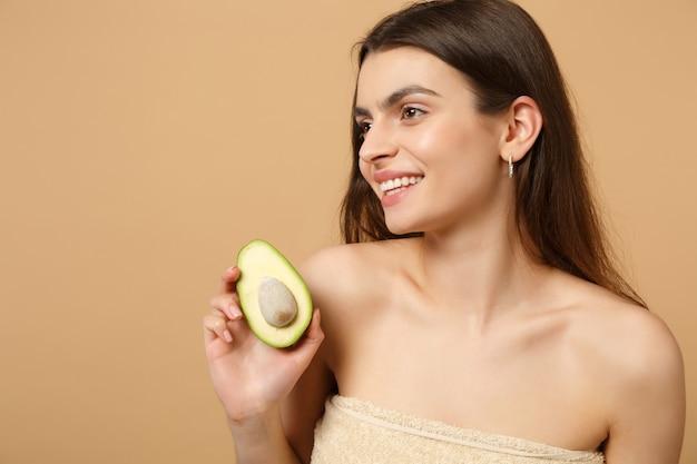 Close-up brunette half naakte vrouw met perfecte huid naakt make-up houdt avocado geïsoleerd op beige pastel muur
