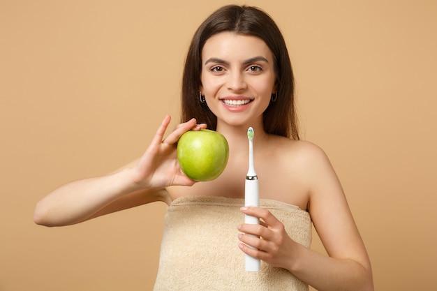 Close-up brunette half naakte vrouw met perfecte huid, naakt make-up houdt borstel geïsoleerd op beige pastel muur