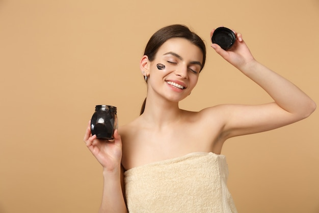 Close-up brunette half naakte vrouw met perfecte huid, naakt make-up zwart masker geïsoleerd op beige pastel muur