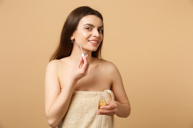 Close-up brunette halfnaakte vrouw met perfecte huid, naakt make-up breng olie uit fles aan op gezicht geïsoleerd op beige pastel muur