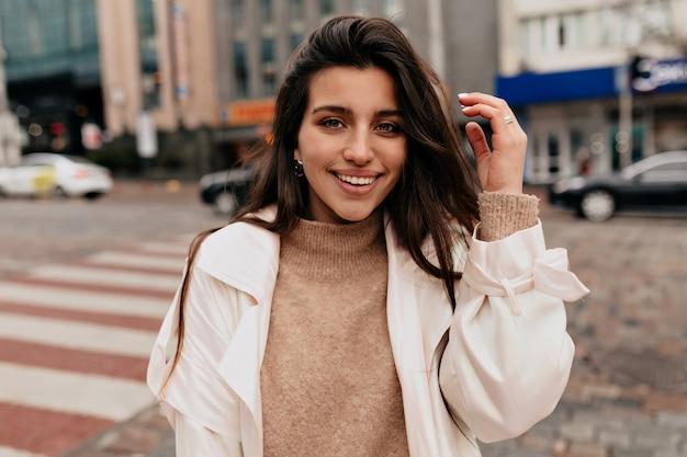 Close-up buiten portret van lachende mooie vrouw met donker haar beige trui en witte jas dragen op straat lopen