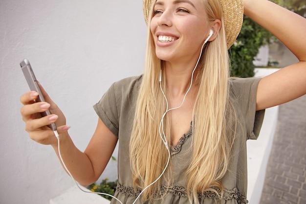 Close-up buiten portret van mooie blonde langharige vrouw met koptelefoon met haar mobiele telefoon in de hand, breed glimlachend en vooruitkijkend