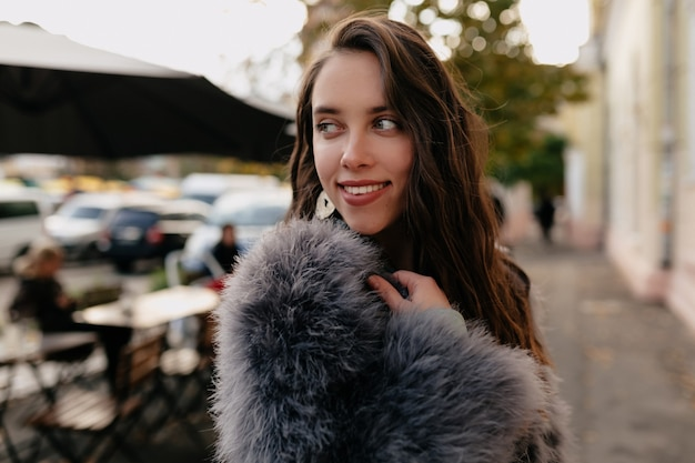 Close-up buiten portret van verlegen charmante vrouw met donker haar en bontjas dragen