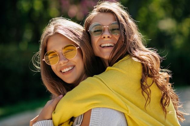 Close-up buiten portret van vriendelijke beste vrienden. blije blonde jonge vrouw in geel overhemd poseren met glimlach naast lachende vriend buiten ontspannen