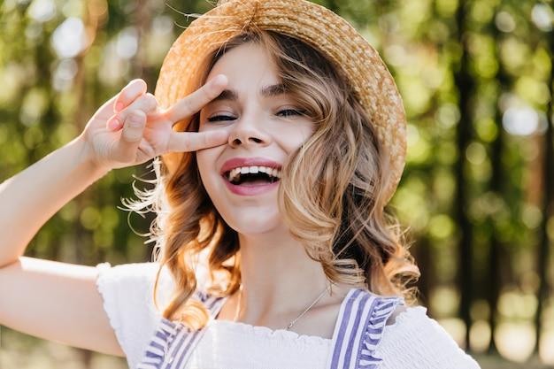 Close-up buiten portret van vrolijk meisje in strooien hoed. betoverende jonge vrouw poseren in bos met vredesteken.