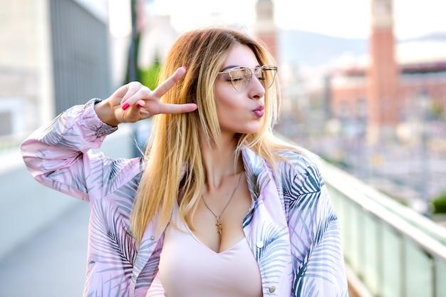 Close-up buiten portret van zalige blonde vrouw, poseren op straat, kus verzenden en vredesgebaar, lentetijd, trendy kleding, zachte getinte kleuren tonen.