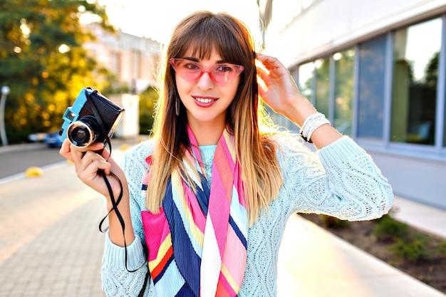 Close-up buiten stad portret van prachtige jonge mooie vrouw met retro vintage filmcamera, pastel trui zonnebril en sjaal, avondzonlicht.