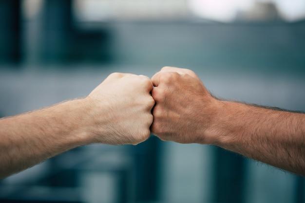 Close-up buitenfoto van twee mannen vuisten bij elkaar te houden