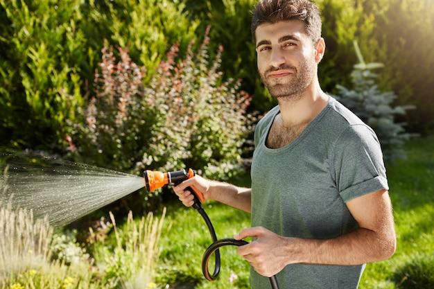 Close-up buitenshuis portret van aantrekkelijke jonge bebaarde spaanse man in blauw t-shirt met ontspannen gezichtsuitdrukking, planten water geven, bladeren snijden.