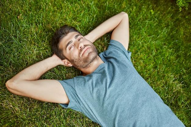Close-up buitenshuis portret van jonge aantrekkelijke volwassen bebaarde spaanse man in blauw t-shirt in de camera kijken, liggend op de grond met ontspannen gezichtsuitdrukking.