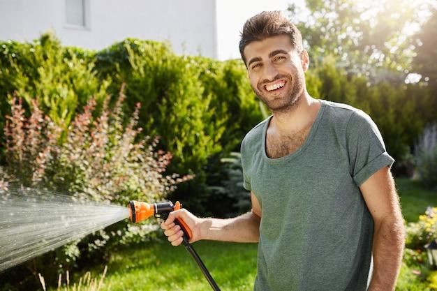 Close-up buitenshuis portret van jonge knappe kaukasische mannelijke tuinman glimlachend planten water geven, zomer doorbrengen in plattelandshuis.