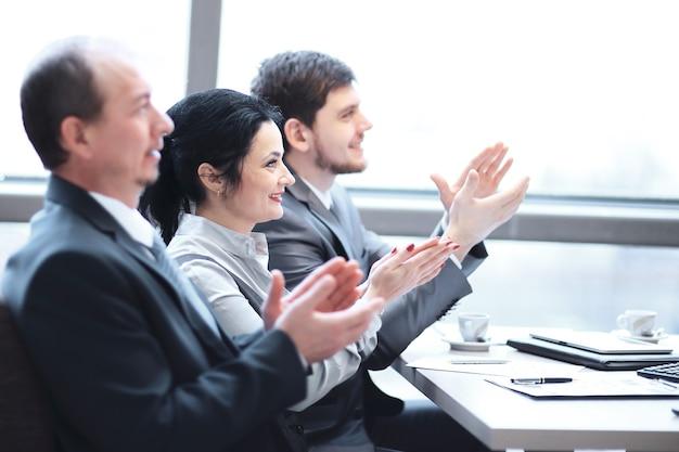 Close-up. business team applaudisseren de spreker, zittend op de werkplek.