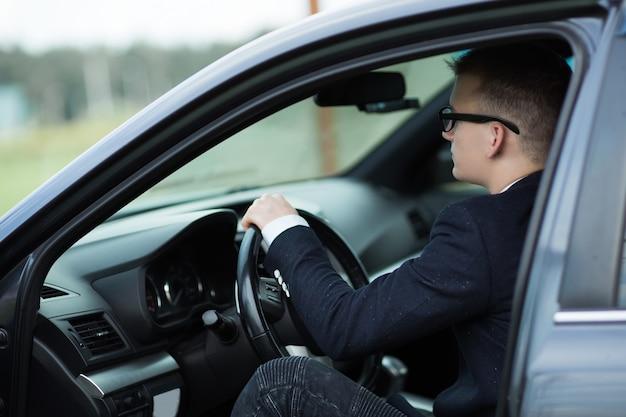 Close up.businessman zit achter het stuur van een prestigieuze auto. het concept van levensstijl