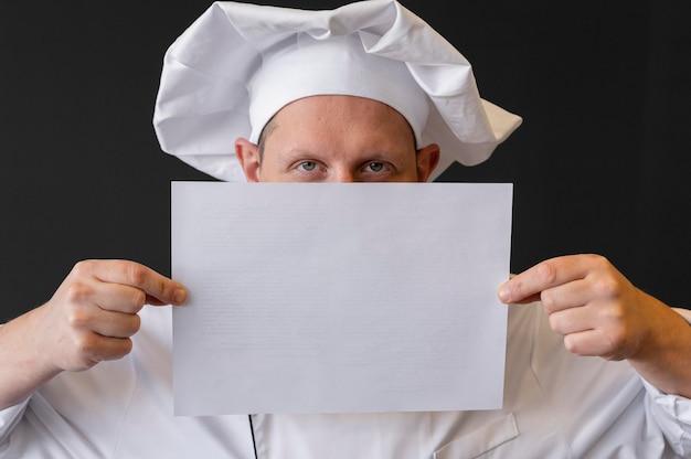 Close-up chef-kok papier blad houden