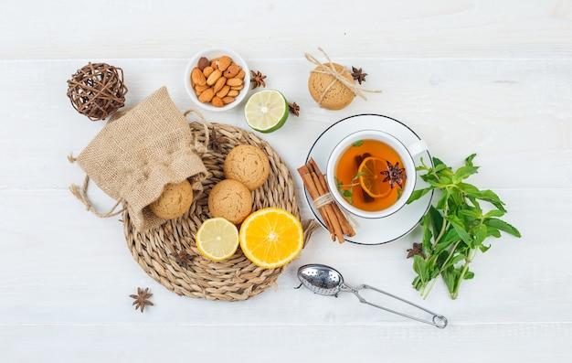Close-up citrusvruchten en koekjes in rieten placemat met kruidenthee en theezeefje,