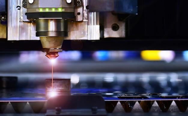 Close-up cnc-lasergesneden machine tijdens het snijden van het plaatmetaal met het vonkende licht.het uiterst nauwkeurige plaatsnijproces door lasersnijden