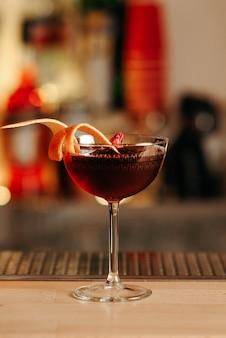 Close-up, cocktail met sinaasappelschil en rosebud