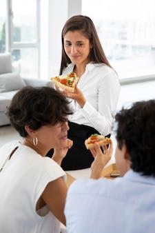 Close-up collega's met pizza