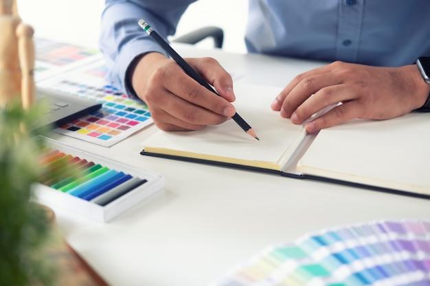 Close-up creatief werken met potlood en schetsboek over stijlvolle creatieve werkruimte.